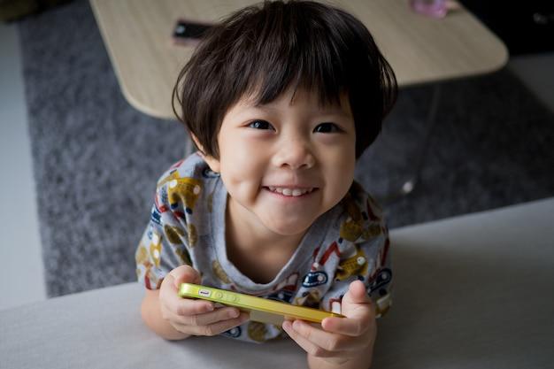 Enfant chinois accro, téléphone, fille asiatique jouant smartphone, enfant utiliser téléphone, regarder un smartphone, regarder des dessins animés Photo Premium
