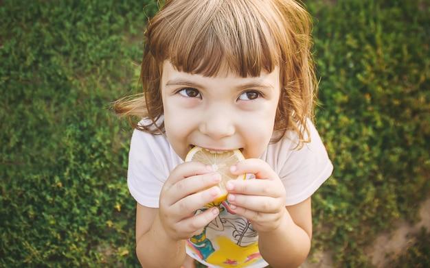 Enfant avec un citron. mise au point sélective. nourriture et boisson. Photo Premium