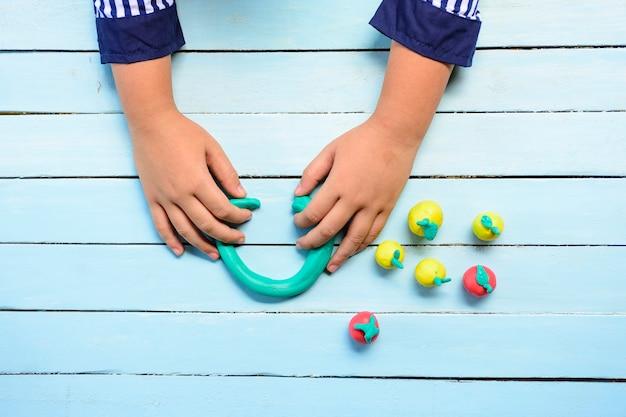 Enfant avec clay et utilisant la créativité pour faire la ligne verte et etc. Photo Premium