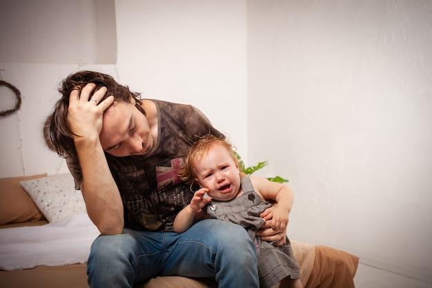 L'enfant Crie, Hystérique. Le Parent Est Irrité, Fatigué Photo Premium