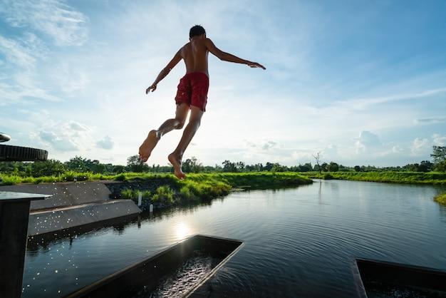 Enfant dans les airs en sautant dans le lac avec un beau rayon de soleil - paysage de nature estivale Photo Premium