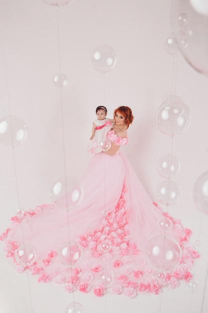L'enfant dans les bras de sa mère vêtu d'une robe rose à fleurs Photo Premium