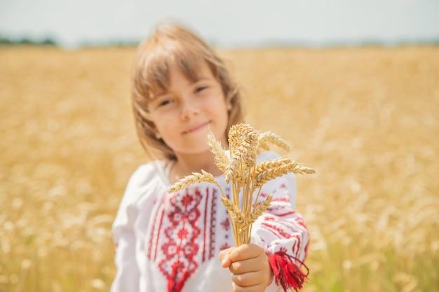 Un enfant dans un champ de blé dans une chemise brodée. Photo Premium