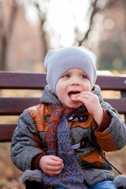 Un enfant dans le parc en train de manger du mandarin Photo Premium