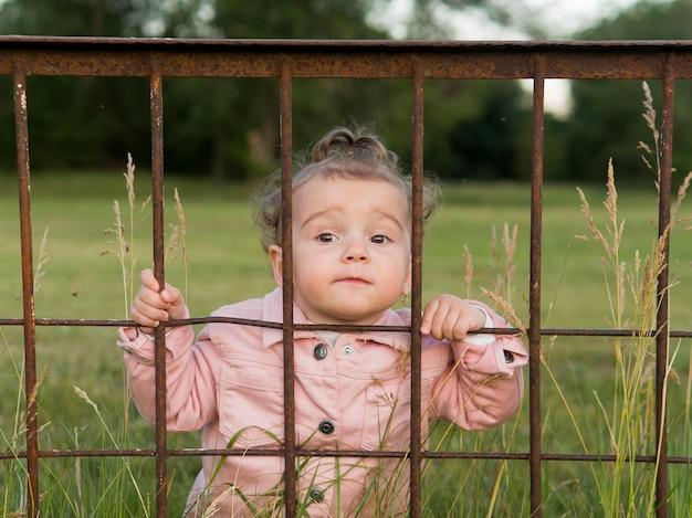 Enfant, Dans, Rose, Vêtements, Derrière, Parc, Barres, Vue Frontale Photo gratuit