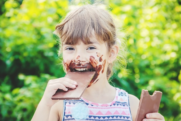 Un enfant à la dent sucrée mange du chocolat. mise au point sélective. Photo Premium
