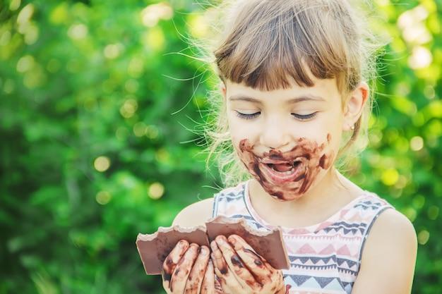 Un enfant à la dent sucrée mange du chocolat. mise au point sélective. Photo Premium
