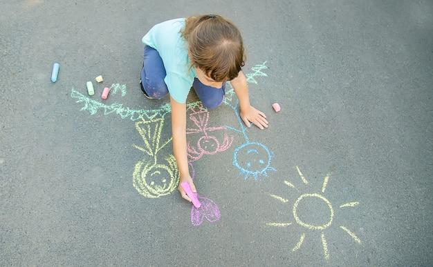 Enfant dessine une famille sur le trottoir avec de la craie. mise au point sélective. Photo Premium