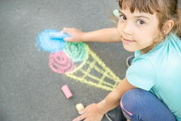 Enfant dessine la glace sur l'asphalte à la craie. mise au point sélective. Photo Premium