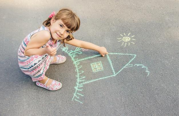 L'enfant dessine la maison à la craie sur l'asphalte. mise au point sélective. Photo Premium