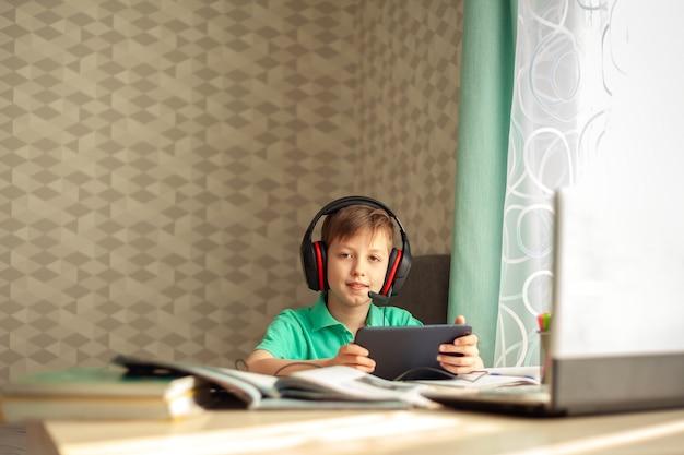 L'enfant à Distance Dans Les écouteurs Regarde Une Leçon Sur Une Tablette. L'éducation En Ligne Concept. Photo Premium