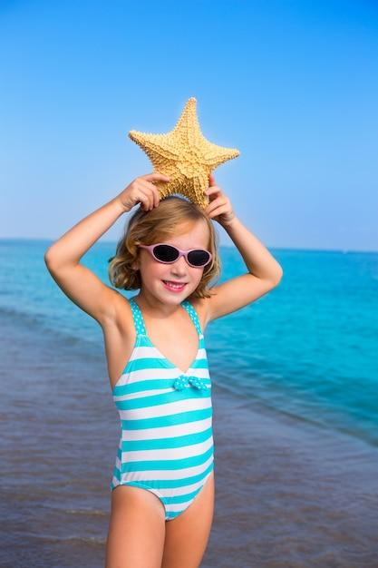 Enfant enfant fille en été plage vacances avec étoile de mer Photo Premium