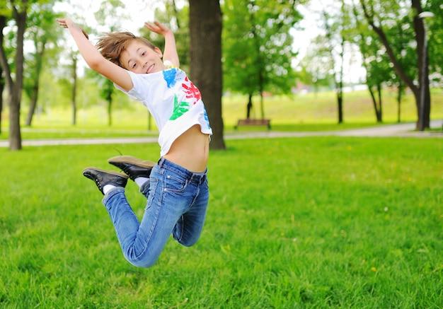 L'enfant est barbouillé de doigts colorés peignant des vêtements souriant dans le parc. Photo Premium