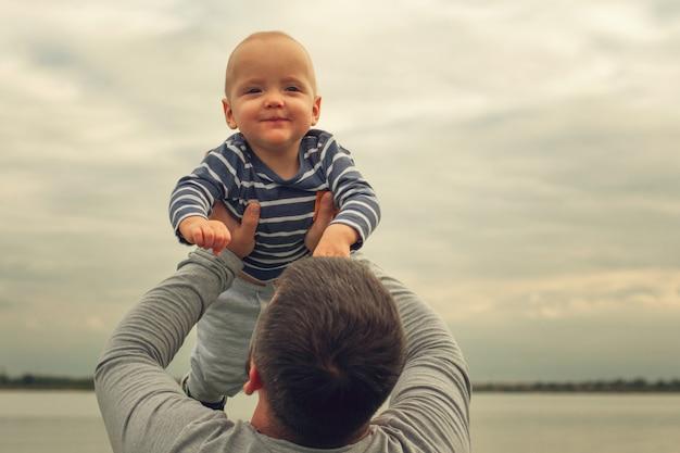 L'enfant est dans les bras du père. enfant sur fond de ciel sur les mains de papa. Photo Premium