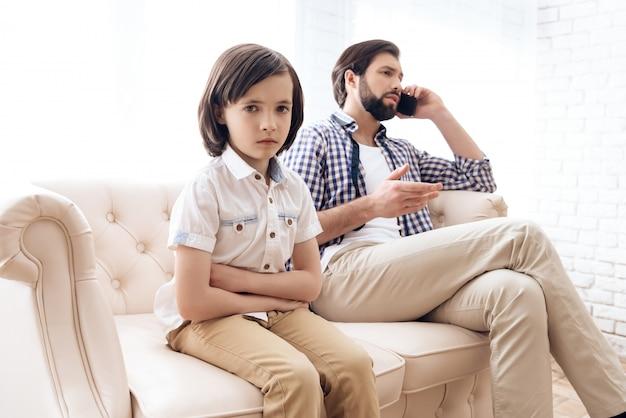 L'enfant était contrarié que papa ne lui prête pas attention. Photo Premium