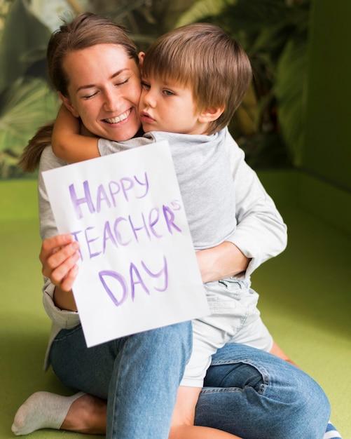 Enfant étreignant Un Enseignant Heureux Photo gratuit