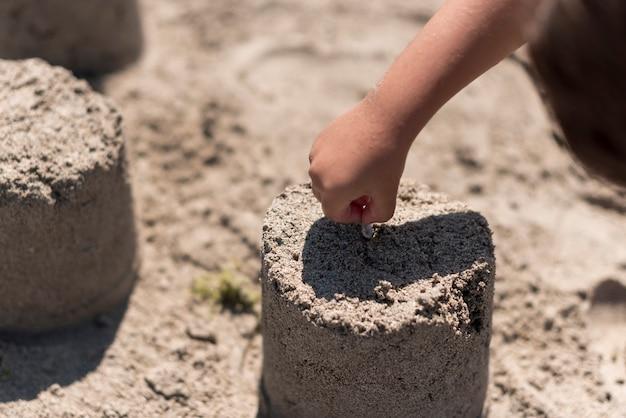 Enfant Faisant Un Château De Sable à La Plage Photo gratuit