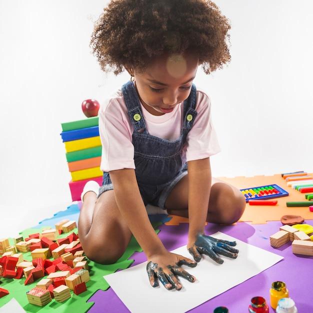 Enfant faisant des empreintes de main sur papier en studio Photo gratuit