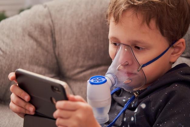 L'enfant fait l'inhalation à la maison. Photo Premium