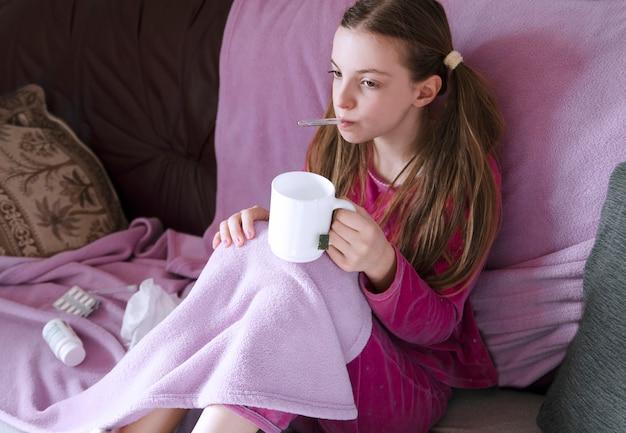 Enfant fille assise dans son lit avec thermomètre dans la bouche sous une couverture et buvant du thé Photo Premium