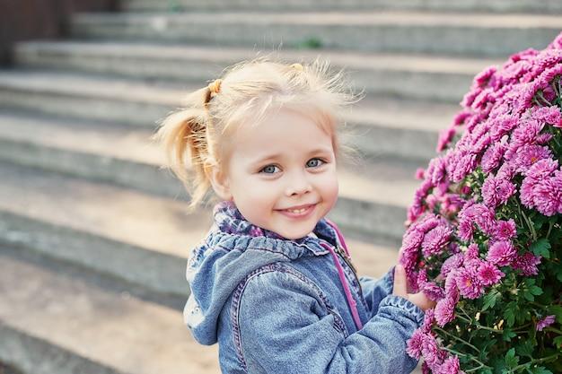 Enfant fille dans un parc près d'un parterre de chrysanthèmes en automne Photo Premium