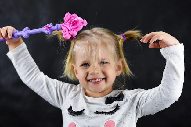 Enfant fille évoque une baguette magique sur un fond noir Photo Premium