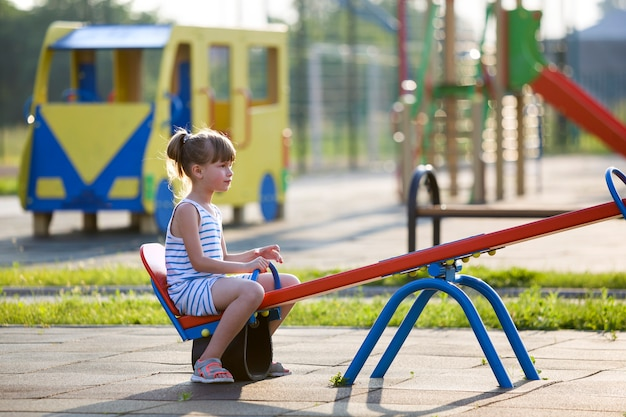 Enfant fille à l'extérieur sur balançoire à balançoire sur une journée d'été ensoleillée. Photo Premium