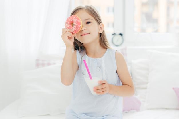 Enfant Fille Pose Dans La Chambre Avec Délicieux Beignet Et Milk-shake Photo Premium