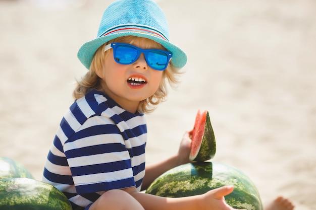 Enfant Gai Souriant Avec Pastèque Sur Le Bord De Mer. Joli Petit Garçon Sur La Plage, Manger De La Pastèque. Enfant Souriant Heureux. Photo Premium
