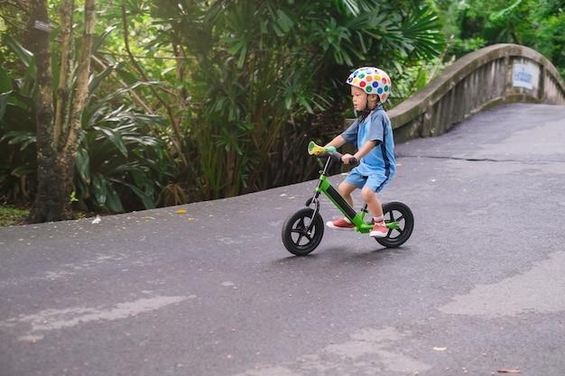 Enfant garçon bambin portant casque de sécurité équitation équilibre vélo bas d'une colline Photo Premium