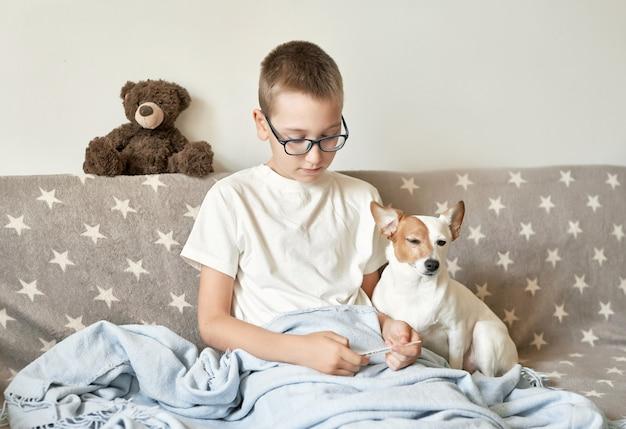 Enfant garçon avec chien jack russell terrier assis sur le canapé, le garçon a un rhume Photo Premium
