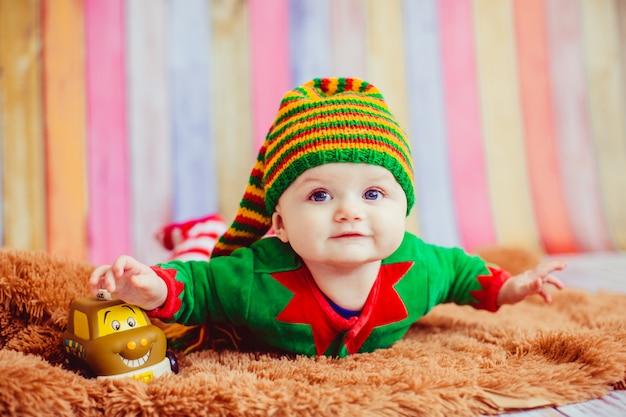 Enfant habillé comme un elfe repose sur un tapis moelleux Photo gratuit