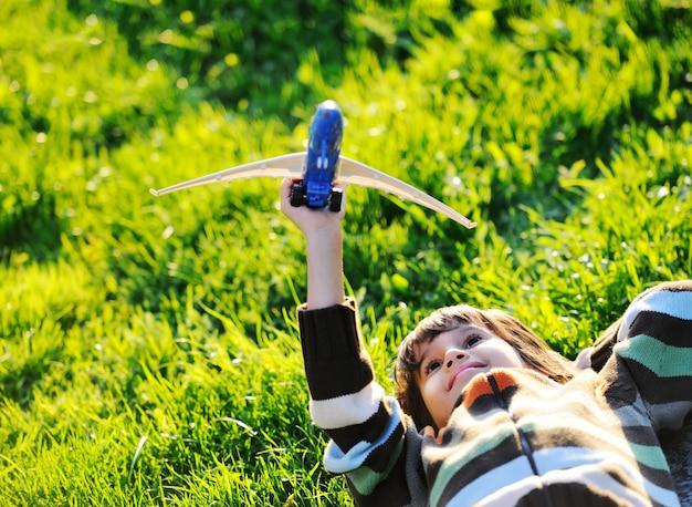 Enfant heureux, appréciant ensoleillé fin d'été et journée d'automne dans la nature sur l'herbe verte Photo Premium