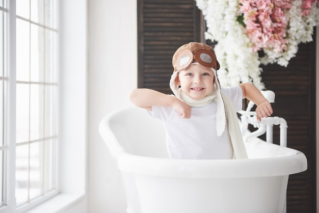 Enfant heureux en chapeau de pilote jouant dans la salle de bain. enfance. fantaisie, imagination. Photo Premium