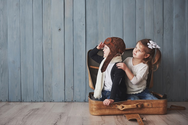 Enfant heureux en chapeau de pilote et petite fille jouant avec une vieille valise. enfance. fantaisie, imagination. voyage Photo Premium