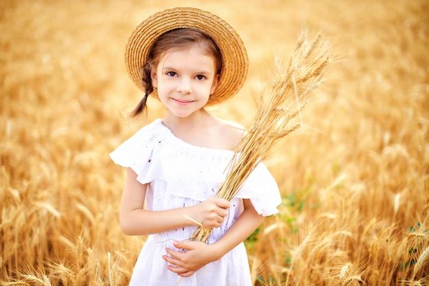 Enfant heureux dans le champ de blé d'automne. belle fille en robe blanche et chapeau de paille s'amuser avec jouer, récolter Photo Premium