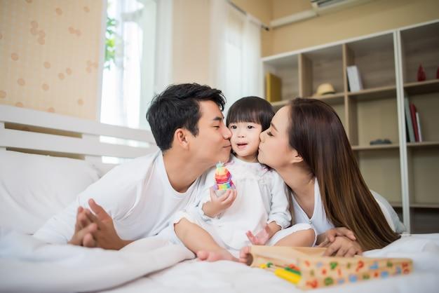 Enfant heureux avec les parents jouant dans le lit à la maison Photo gratuit