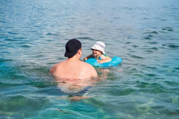 Un enfant heureux avec son père nage dans un anneau de natation dans la mer Photo Premium