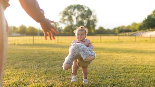 Enfant Heureux En Vêtements Roses Et Ours En Peluche Long Shot Photo gratuit