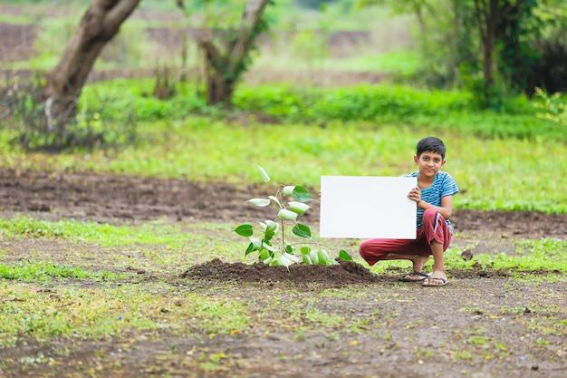 Enfant indien tenant une affiche vide Photo Premium