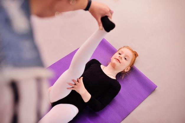 Enfant - la jolie ballerine rousse effectue des exercices d'étirement à l'école de ballet Photo Premium