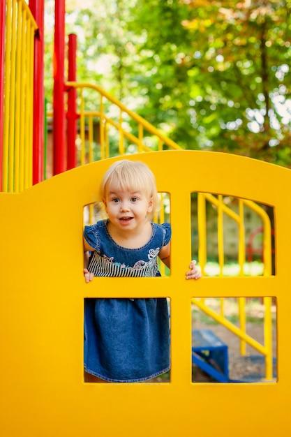 Enfant jouant sur une aire de jeux extérieure. petite fille joue sur le jardin de l'école ou de la maternelle Photo Premium