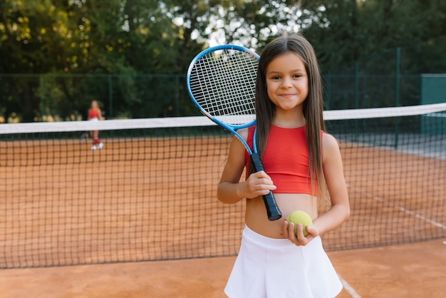 Enfant Jouant Au Tennis Sur Un Court Exterieur Petite Fille Avec Raquette De Tennis Et Balle Au Club De Sport Exercice Actif Pour Les Enfants Photo Premium