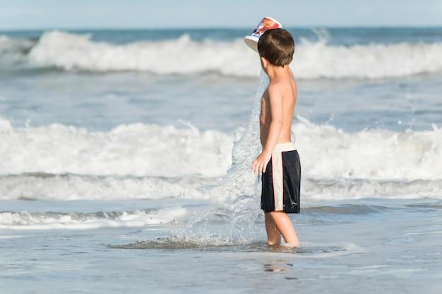 Enfant jouant sur le bord de la mer dans l'eau Photo gratuit