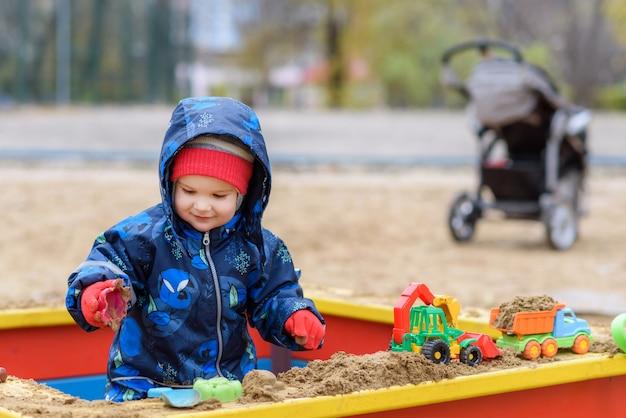 L'enfant joue aux voitures sur le terrain de jeu Photo Premium