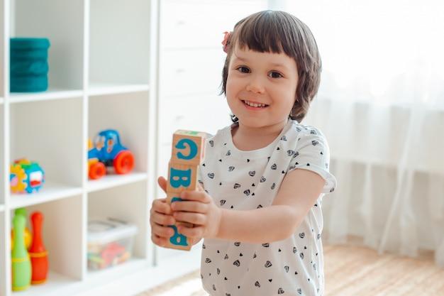 Enfant joue avec des blocs de bois avec des lettres sur le sol dans la pièce où une petite fille construit une tour chez elle ou à la maternelle. Photo Premium