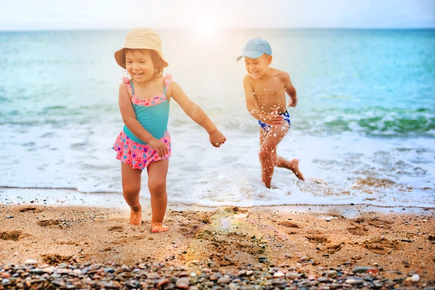L'enfant joue et éclabousse dans la mer Photo Premium