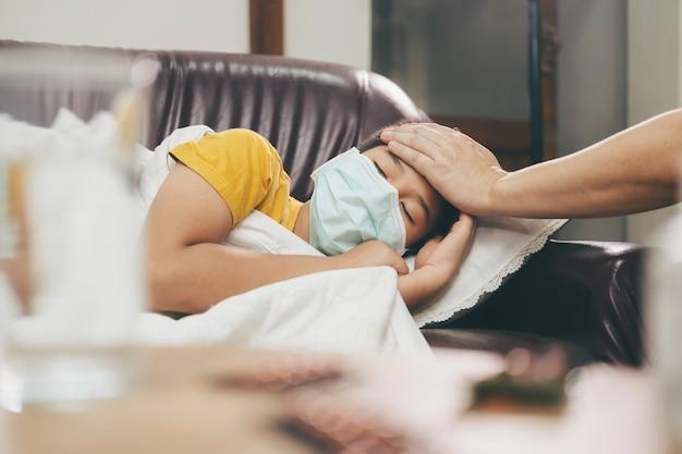 Enfant Malade Couché Dans Le Canapé-lit Avec Un Masque De Protection Sur Le Visage Contre L'infection Photo Premium
