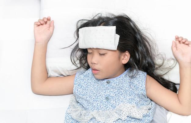 Enfant malade avec une forte fièvre couché dans son lit. Photo Premium