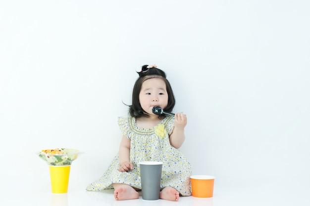 L'enfant mange des aliments pour bébé avec une cuillère. il y a un aliment pour bébé autour de ma bouche. Photo Premium